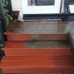 Wood deck back door halfway pressure washed