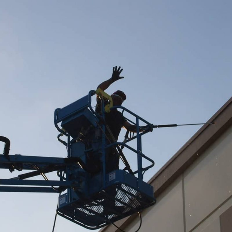 Man on a lift pressure washing in Napa California